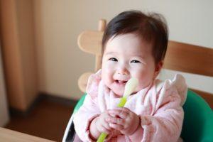 スプーンを持つ笑顔の赤ちゃん